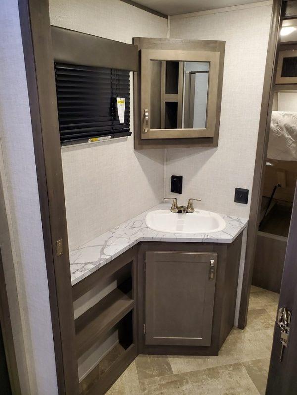 Bathroom vanity in the 2021 Alta Travel Trailers 2350-KRK Rear Kitchen
