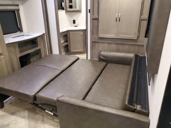 Fold out couch in the 2021 Alta Travel Trailers 2350-KRK Rear Kitchen