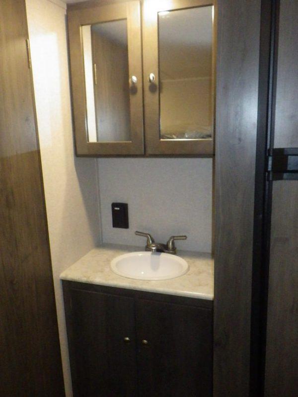 View of the bathroom vanity inside the 2021 Viking 26 Saga Bunk House