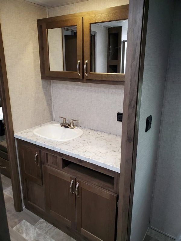 View of the bathroom sink and vanity inside the 2021 Della Terra 312BH Dual Slide Bunk House